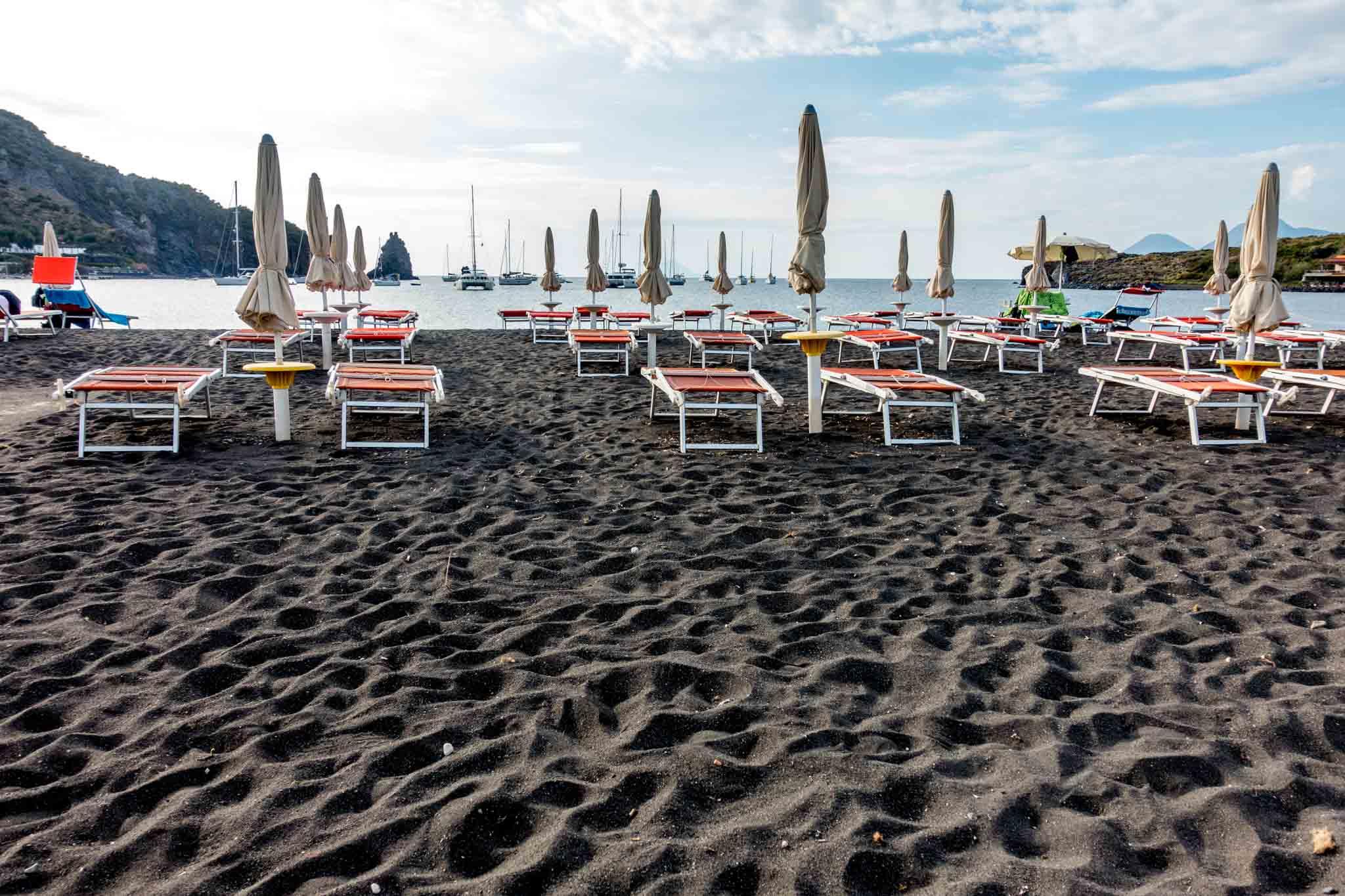 Chairs on black sand beach on Vulcano