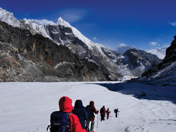 People trekking in Nepal across an ice field.