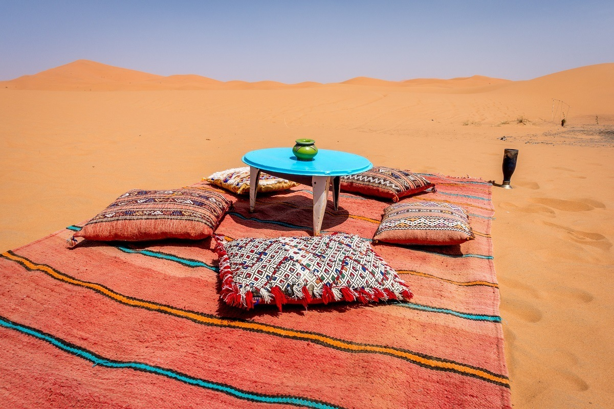 Blanket and table set in sand dune in Merzouga, Morocco