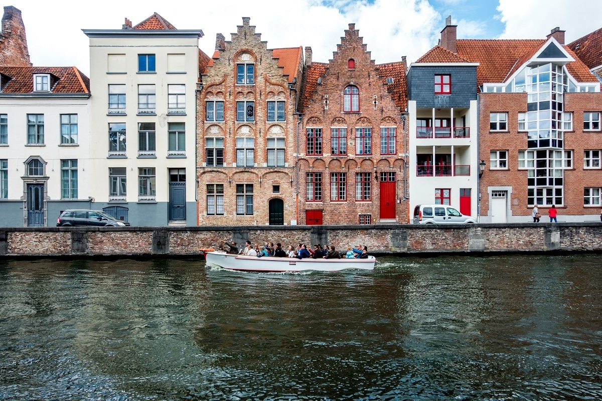 Boat cruising in a canal in front of buildings