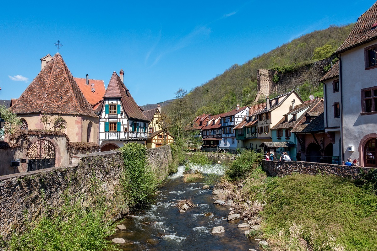 Half-timbered buildings beside river in Kaysersberg, part of the Alsace wine route