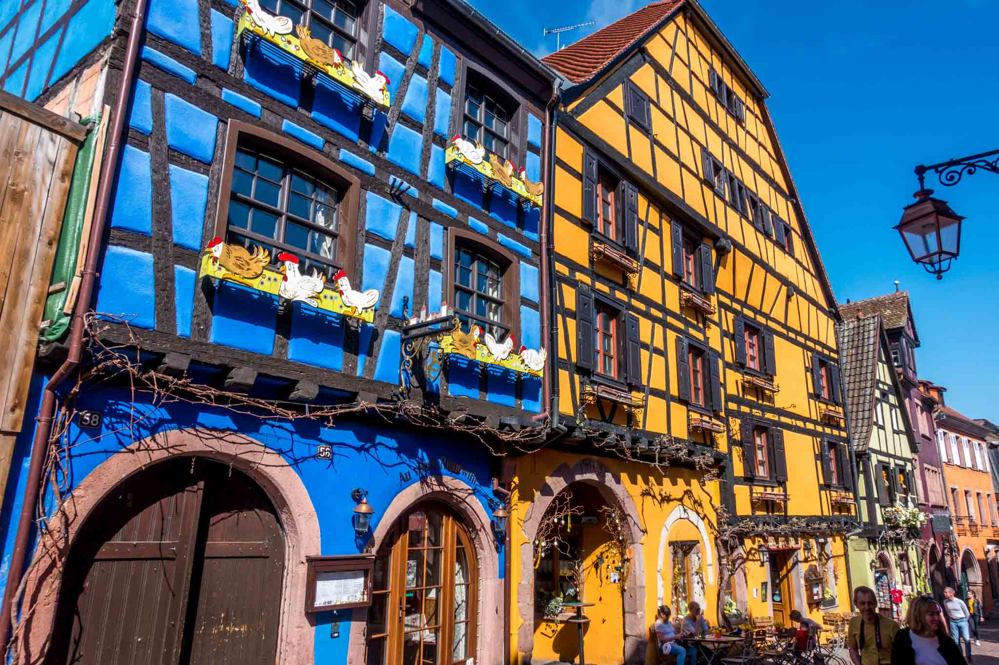 Blue and yellow half-timbered buildings line the streets in Riquewihr, France