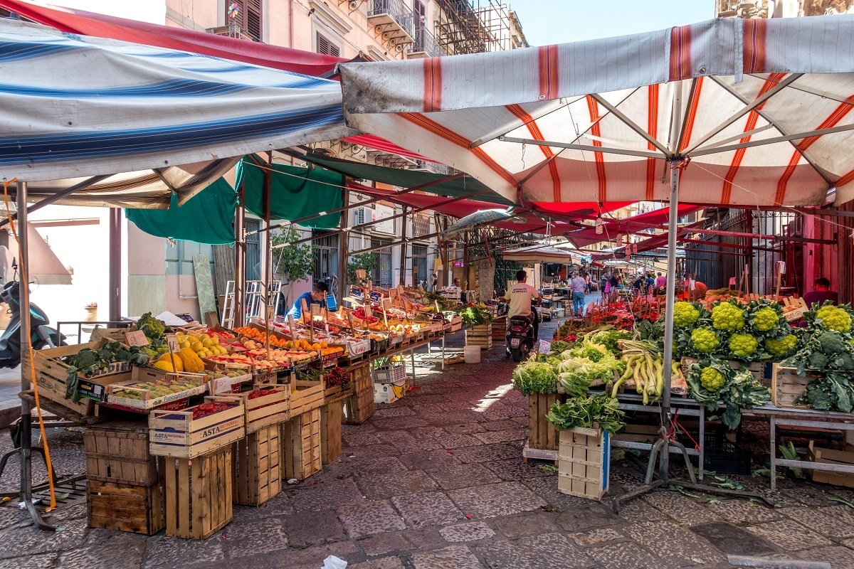 Produce displayed under tents in the middle of the street at Capo market