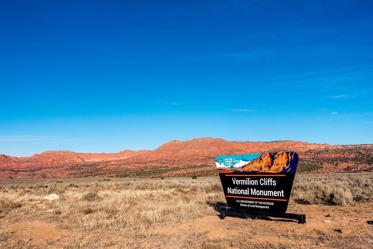 Sign for the Vermilion Cliffs National Monument in front of red hills