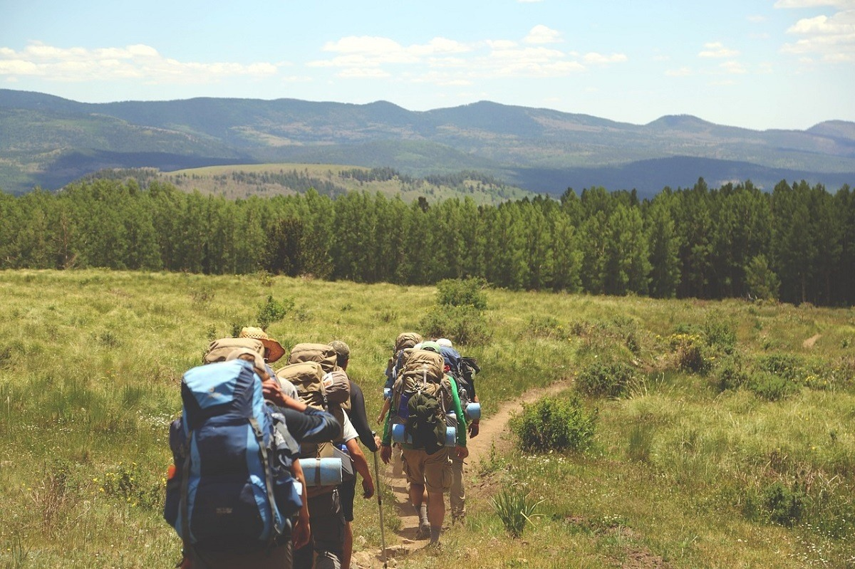 People hiking across a grassy meadow in the mountains with large backpacks