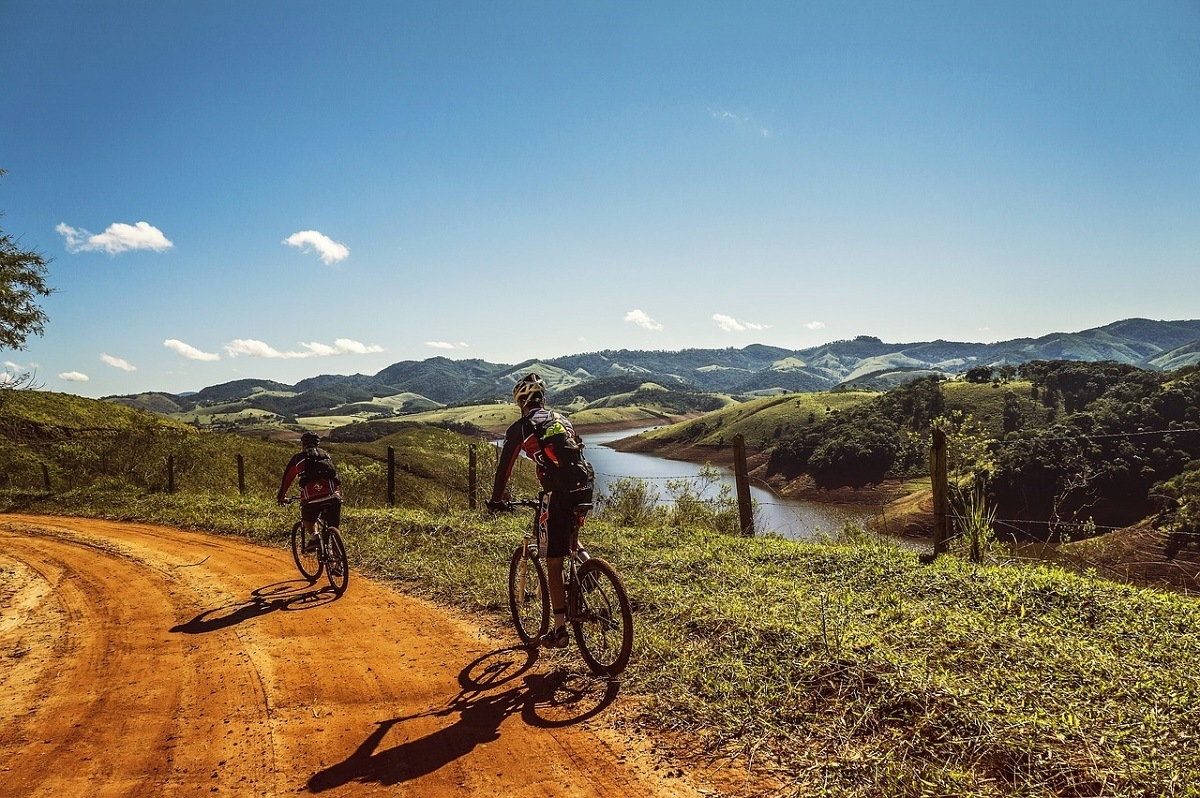 People mountain biking along a dirt road above a river in the rolling hills