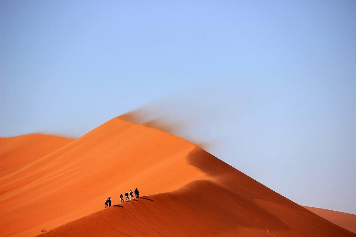 People hiking a giant sand dune in the wind