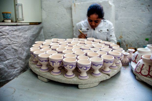 Girl painting pottery, a popular Moroccan souvenir