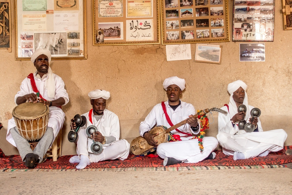 Seated Gnawa musicians performing near Merzouga, Morocco