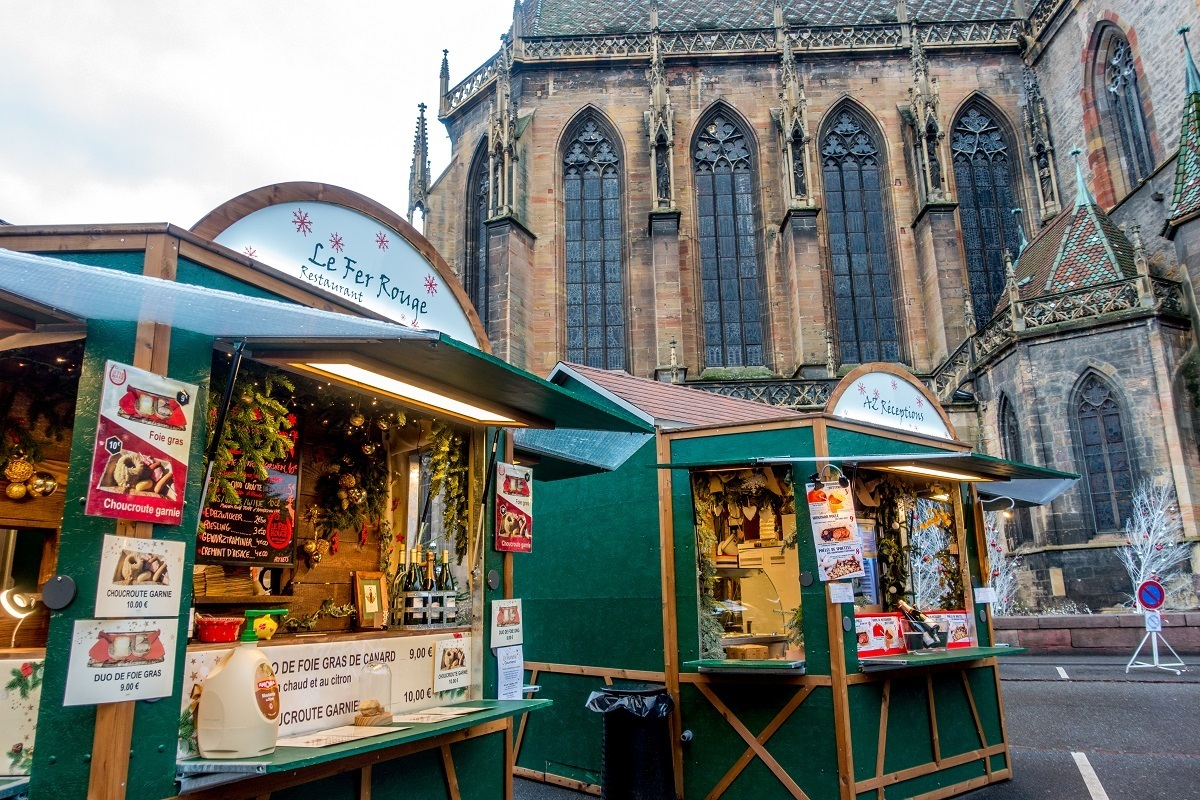 Gourmet food market vendors by cathedral in Colmar