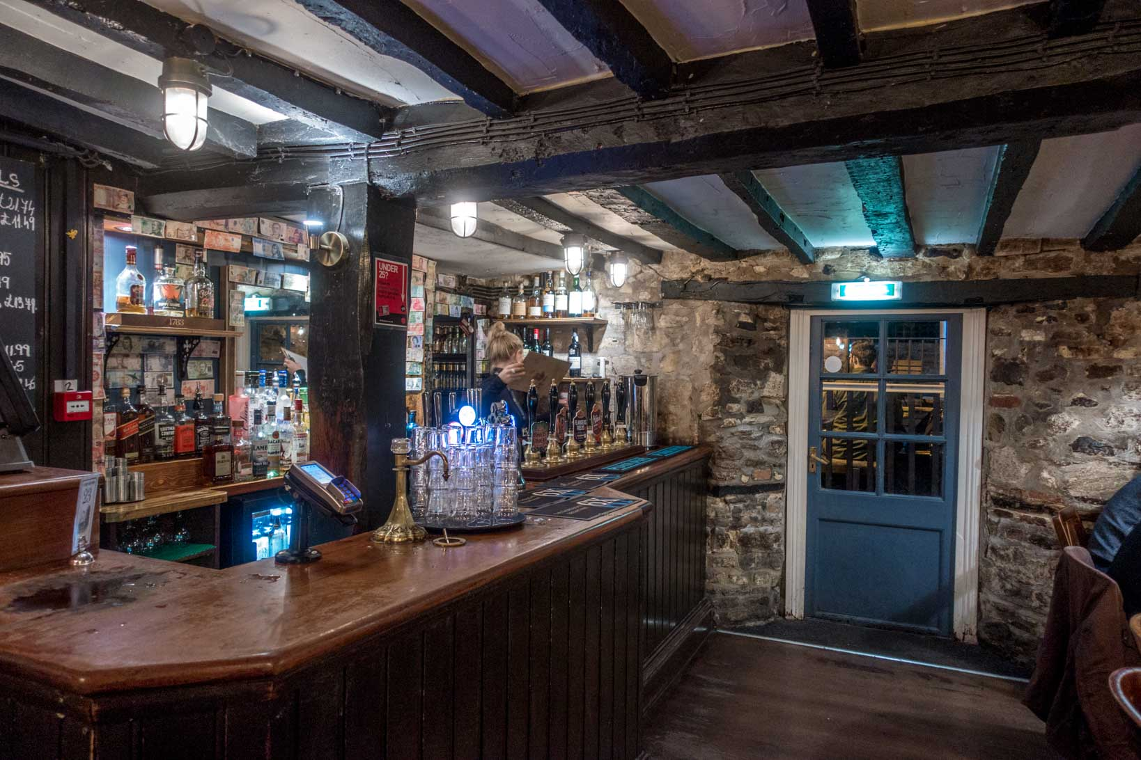 Bar, stone walls, and old wooden beams inside the historic Turf Tavern in Oxford, England