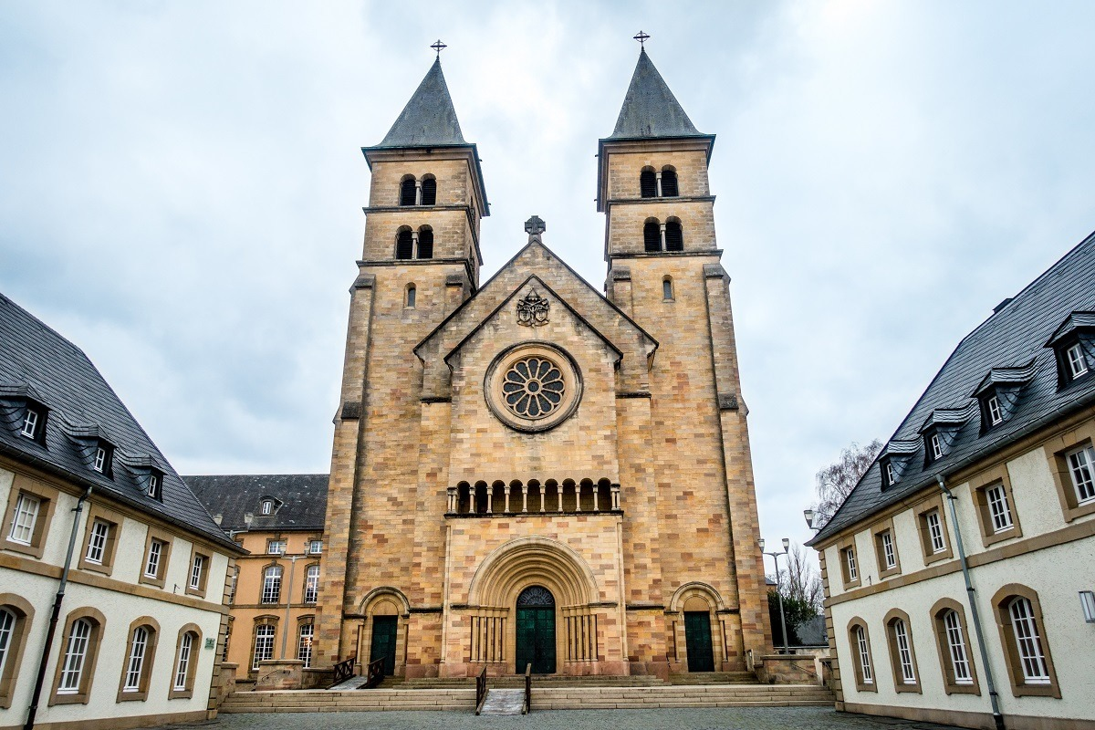 Church exterior with towers and stained glass, Echternach Abbey in Luxembourg