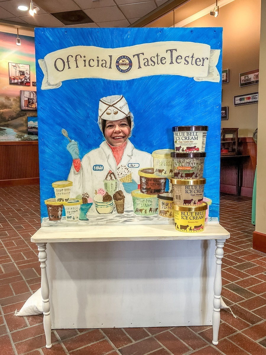 Woman behind photo cut out prop with Blue Bell ice cream containers