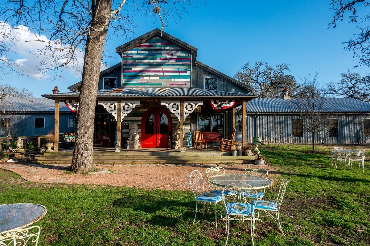 Exterior of barn-like building with table and chairs in yard, Junk Gypsy