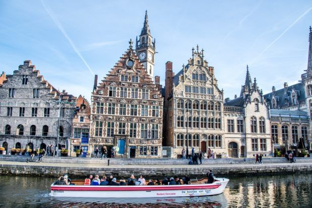 Boat cruising on the river in Ghent Belgium by historic buildings