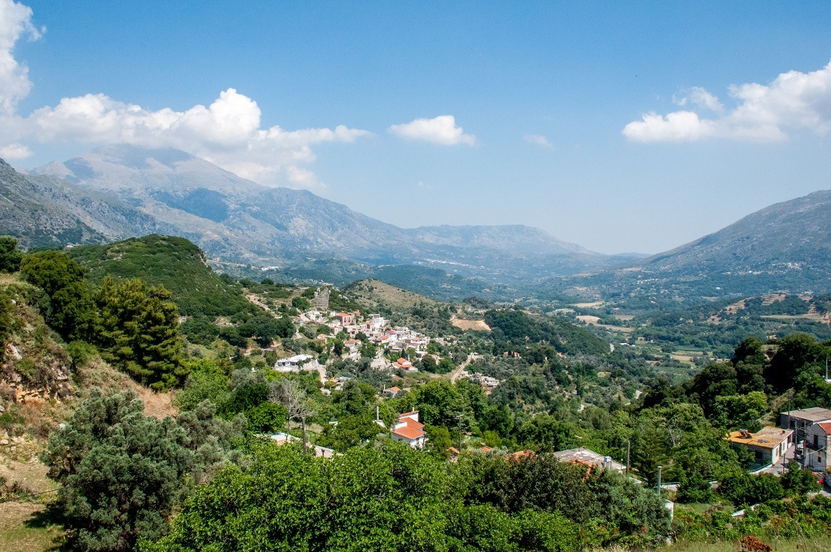 The lush, green mountains dotted with buildings in Crete