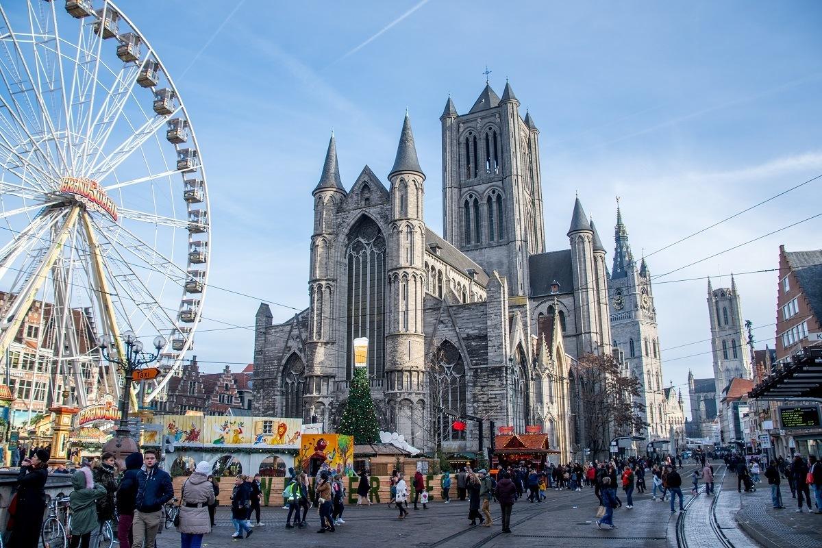 Ferris wheel in front of St. Nicholas Church towers in Ghent, Belgium