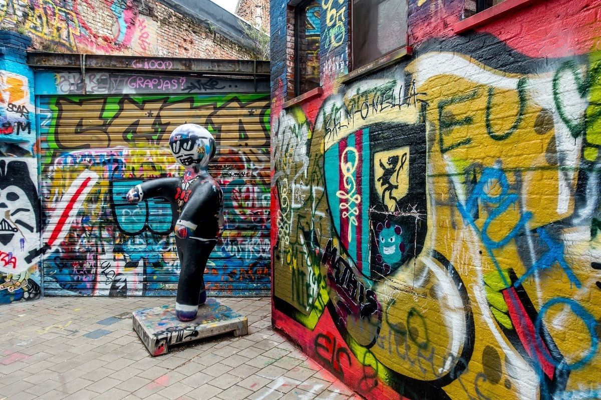 Graffiti-covered alley and spray painted sculpture
