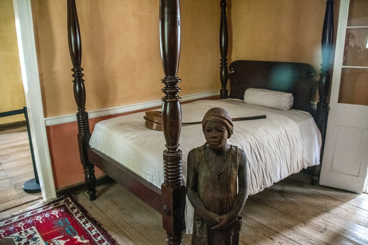 Statue of a child slave next to a bed