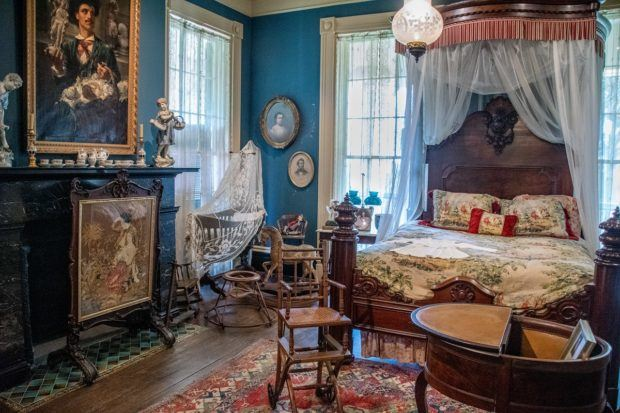 Blue bedroom with numerous portraits in the mansion at Houmas House, one of the south Louisiana plantations