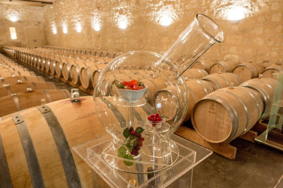 Wine barrel room with a close up of a glass jar filled with fruit