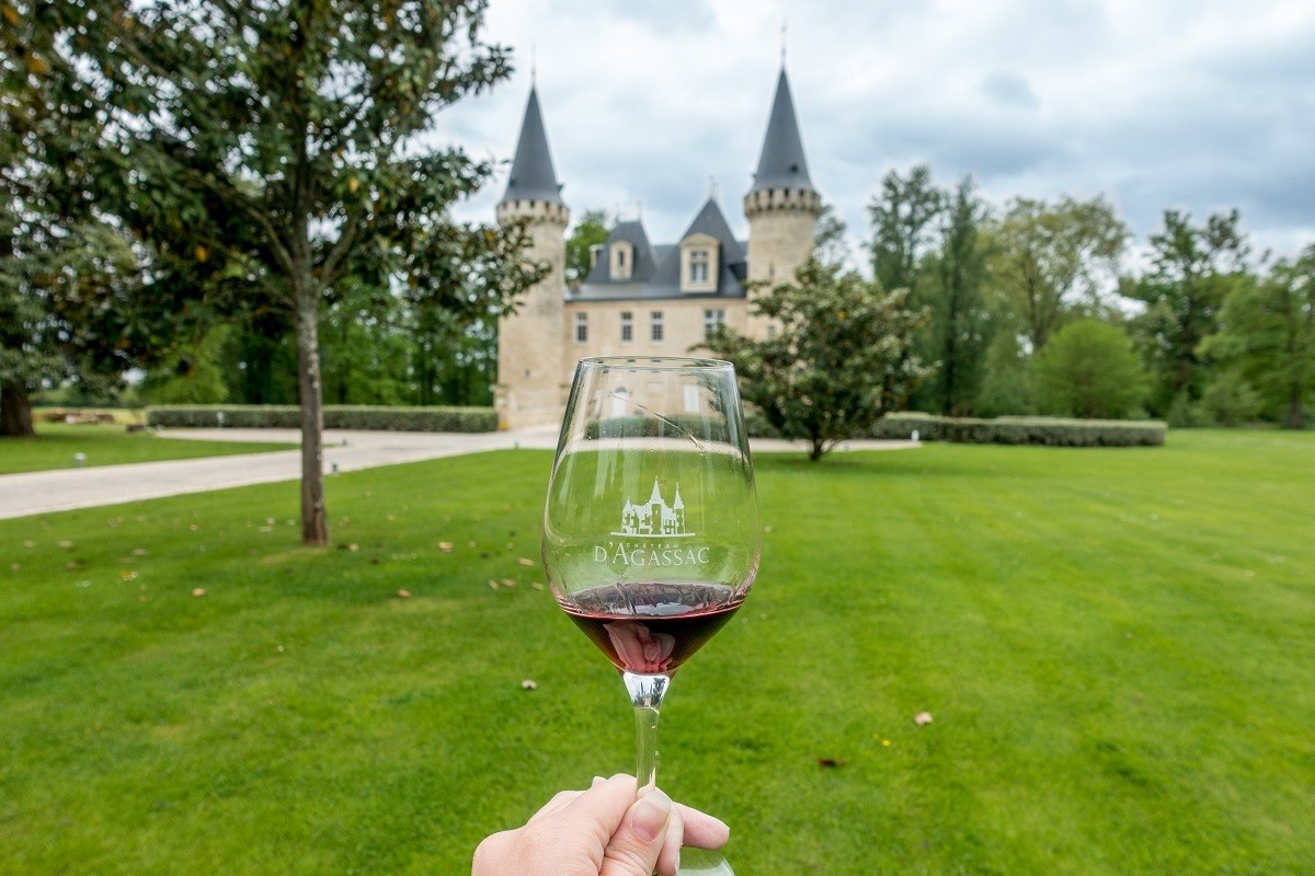 Wine glass held up in front of the exterior of a castle-like building, Chateau d'Agassac