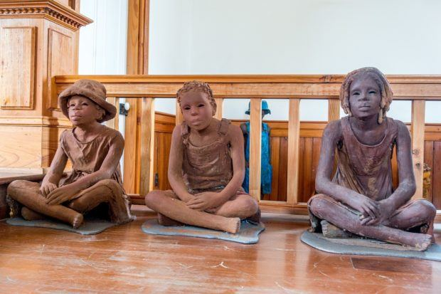 The Children of the Whitney seated on the ground are clay statues that represent child slaves on plantations.
