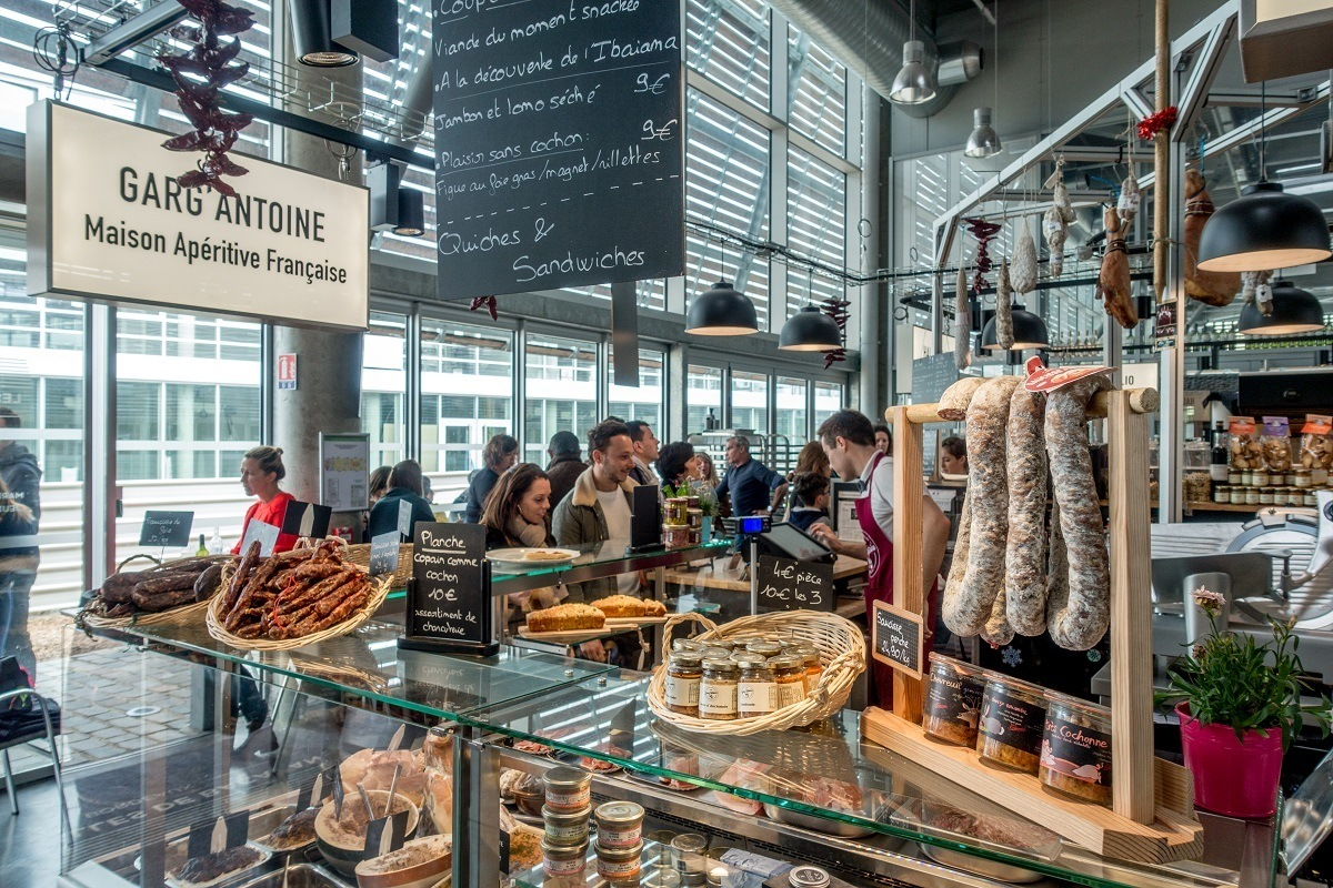 Sausages and jars on a glass counter at Garg'Antoine in a food hall