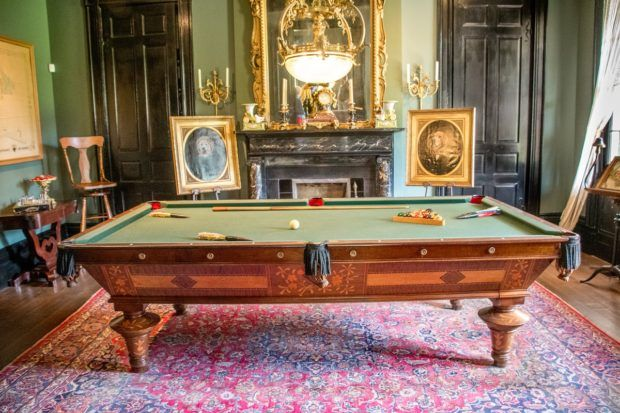 Portraits of dogs flan a pool table in the gentlemen's quarters at Houmas House, formerly one of the largest cane sugar plantations