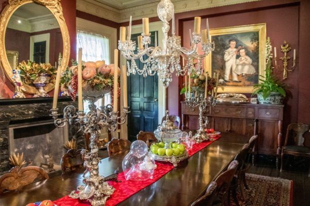 The opulent burgundy dining room with paintings, chandeliers, and candelabras at Houmas House, one of the plantations close to New Orleans