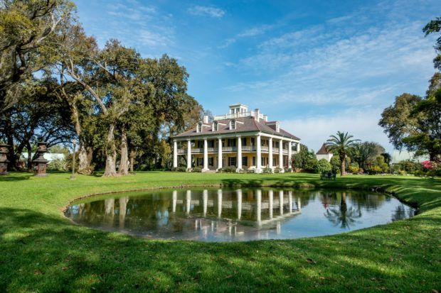 White columned mansion and small pond at Houmas House Plantation, one of the stately plantations near New Orleans