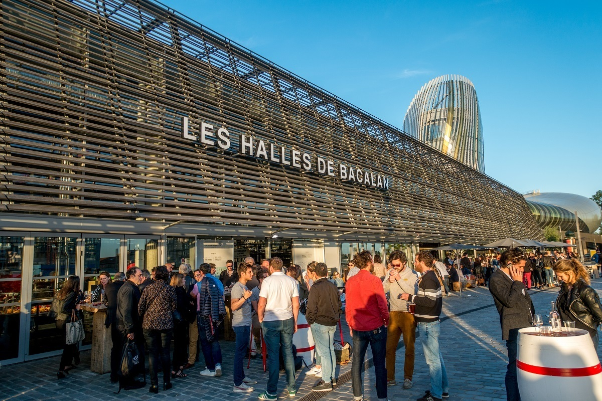 People enjoying happy hour outside a building, the food hall Les Halles de Bacalan
