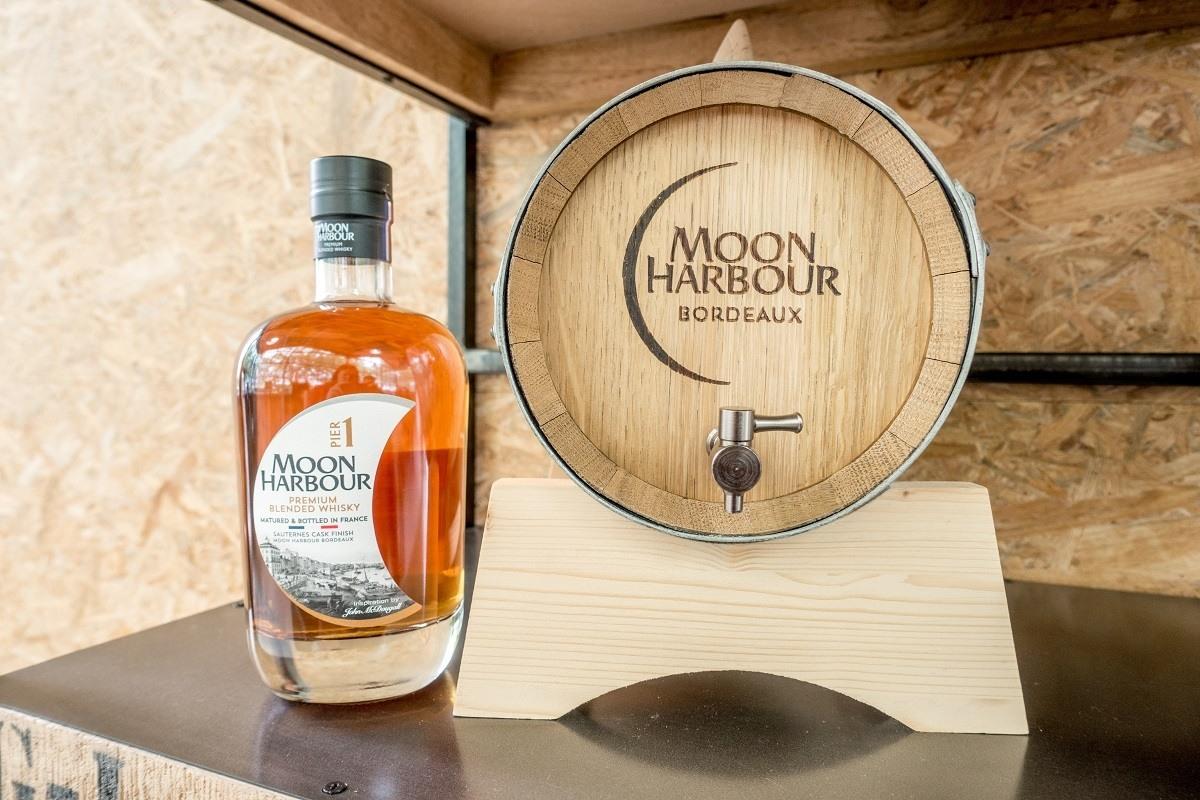 Whiskey bottle on shelf next to mini-barrel from Moon Harbour Distillery