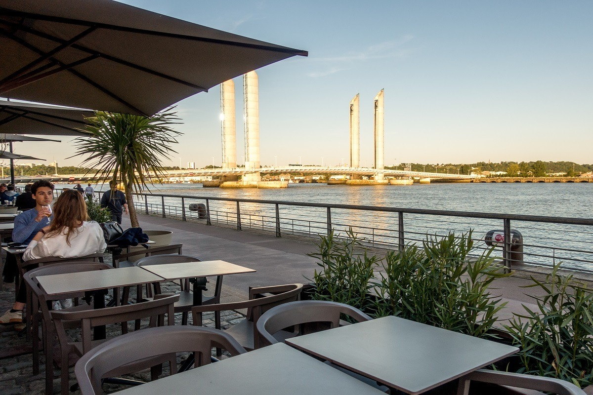 People sitting at an outdoor cafe by the bridge and river in Bordeaux