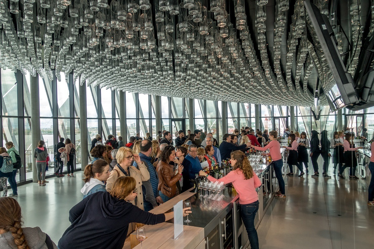 Visitors at wine bar of La Cite du Vin where glass bottles hang from the ceiling