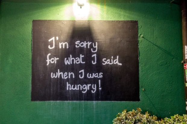 """Black sign on a green wall at a Maltese restaurant says, """"I'm sorry for what I said when I was hungry"""""""