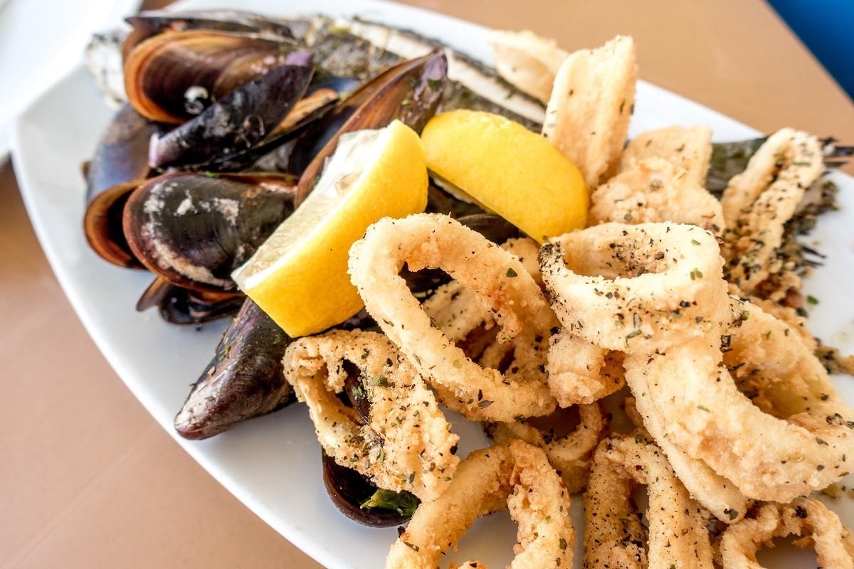 Mussels, calamari, lampuki fish, and lemon on a plate in Maraxlokk, Malta