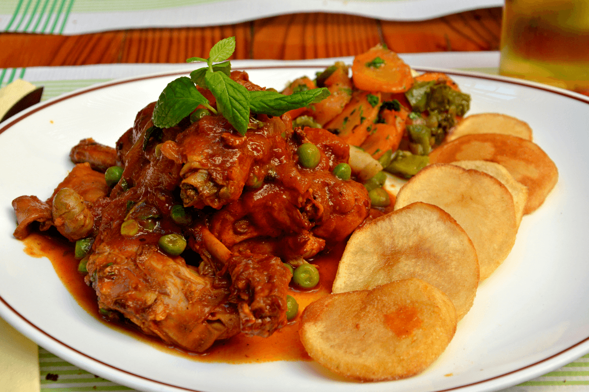 Stewed rabbit served with fried potatoes and vegetables