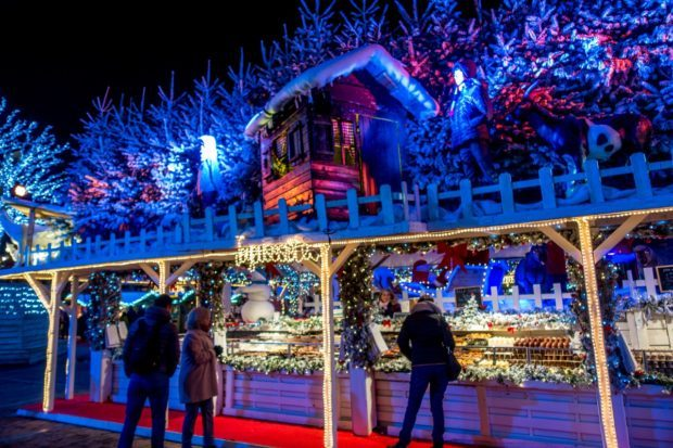 Stand selling candy at the Brussels Christmas market decorated with snow-covered trees and a cabin