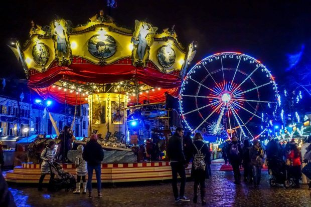 Carousel and Ferris wheel lit up at night at the Brussels Christmas market, a top Belgium market