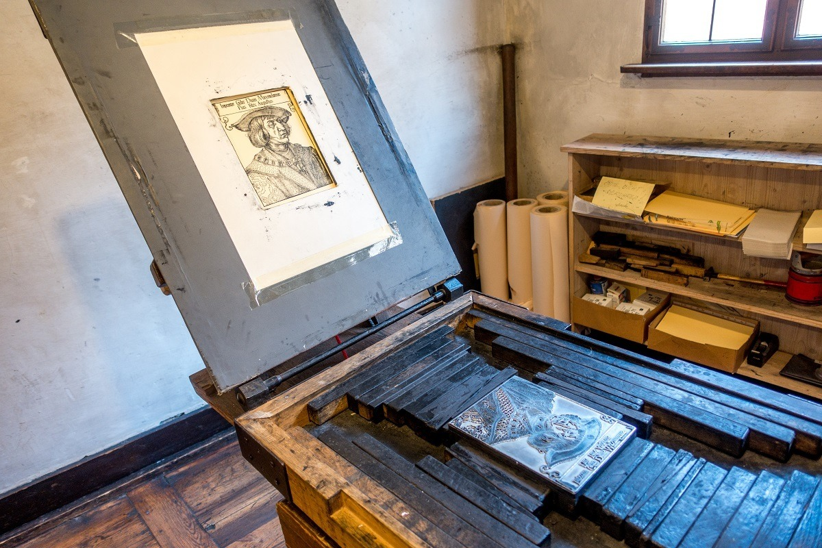 Copper plate engraving press with image of man