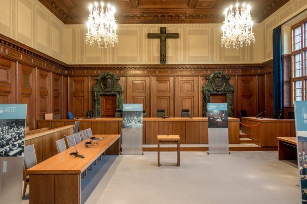 Courtroom 600 where the Nuremberg Trials were held features a judge's bench, place for the defendants, and posters explaining how the room appeared during the famous trials