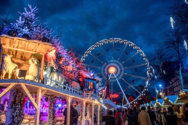 Ferris wheel and food stalls lit up for the Christmas market in Brussels Belgium