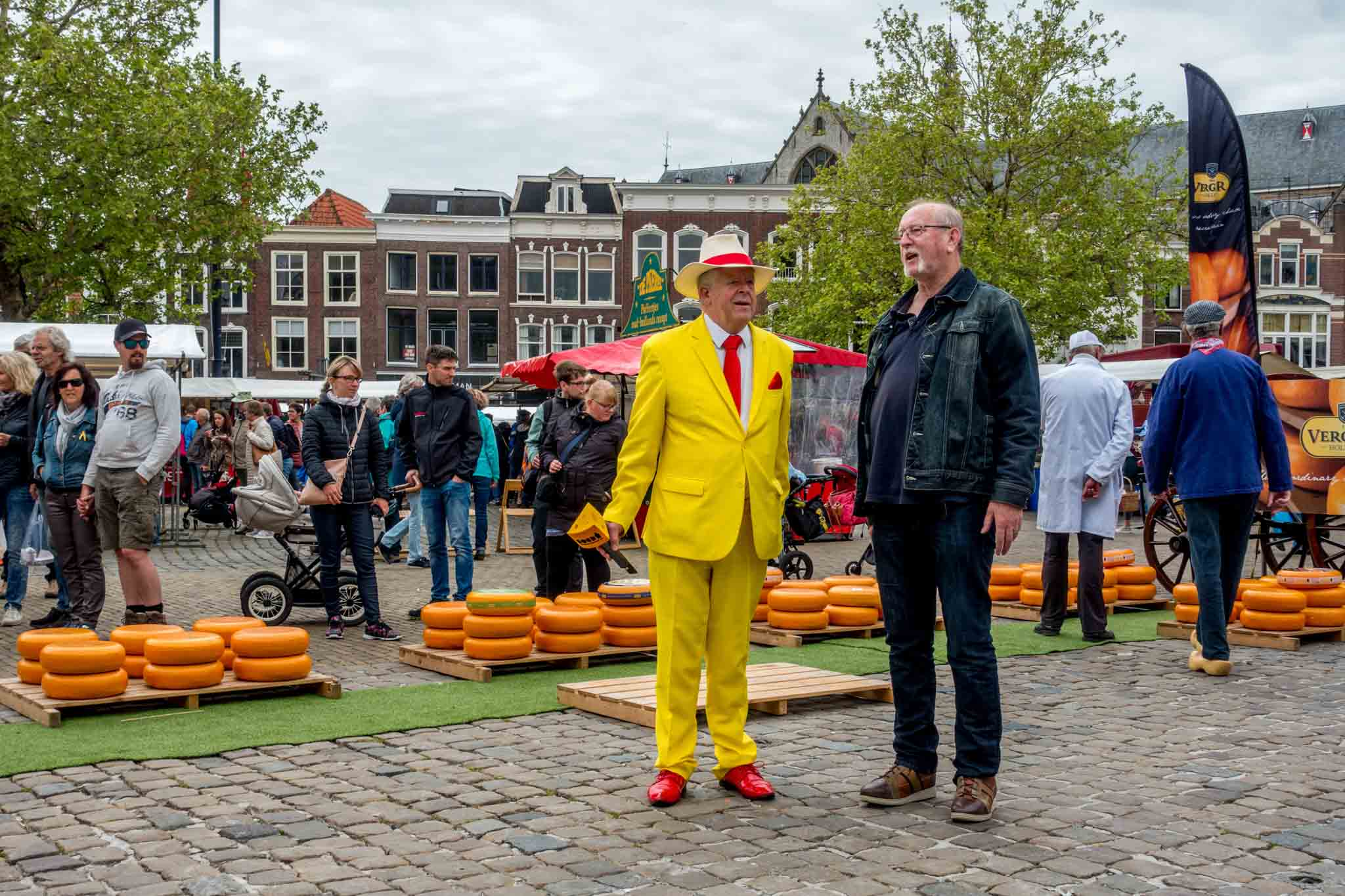 The emcee in a bright yellow suit narrates the Dutch Gouda cheese market Netherlands