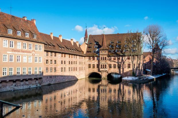 The Hospital of the Holy Spirit is a 14th-century orange brick building stretching across part of the Pegnitz River. It is one of the most photographed places in Nuremberg, Germany.