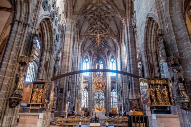 The interior of St. Lorenz Church has vaulted ceilings, medieval carvings of saints, and bright stained glass