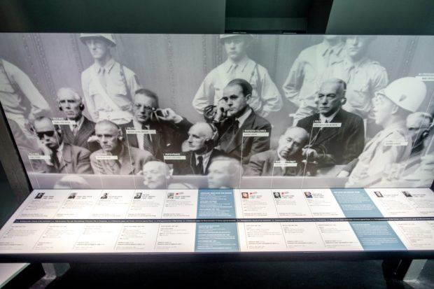 Exhibit at the Palace of Justice features a photograph from the Nuremberg Trials and provides the name of each defendant