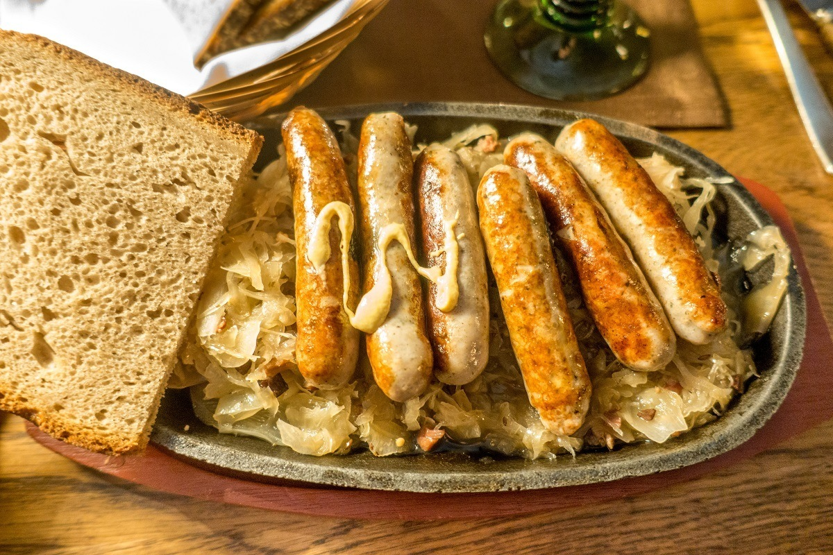 Small Nuremberger sausages served on a pewter plate with sauerkraut and bread