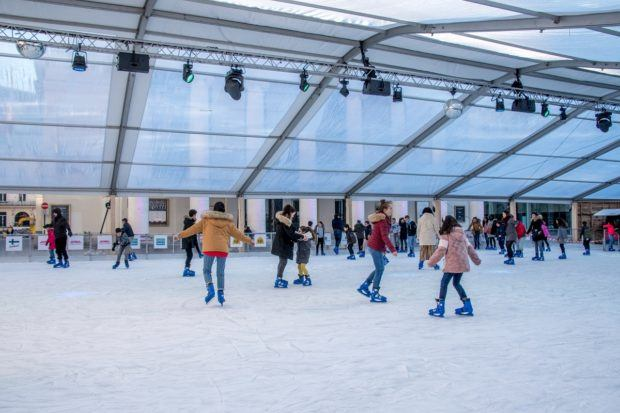 People skating on the covered ice skating rink at Place de la Monnaie in Brussels
