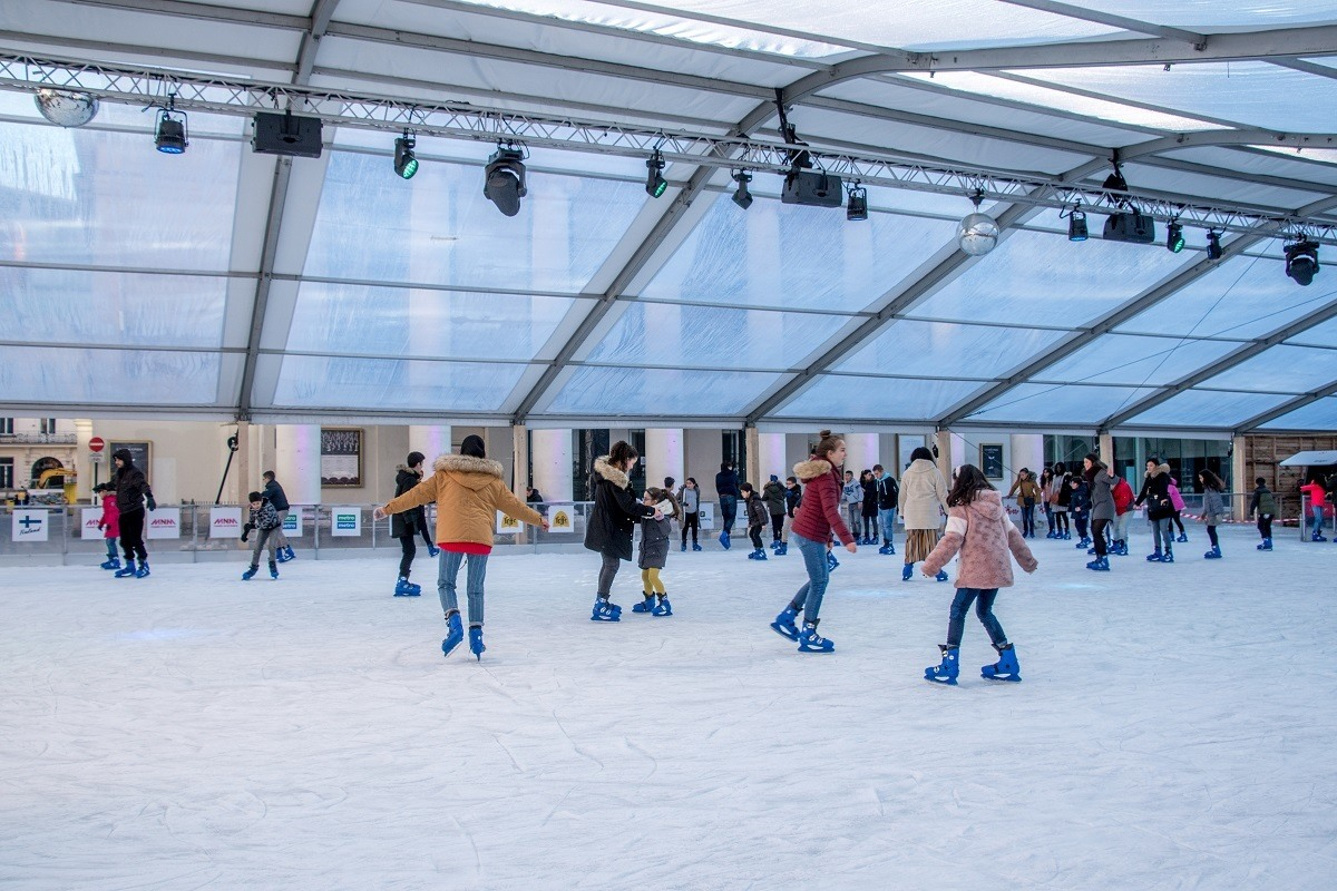 People skating on covered ice skating rink